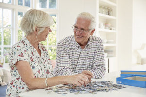 senior man and woman doing puzzle during senior living community activities in boca raton fl
