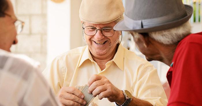 men playing card enjoying the senior living activities at veranda club